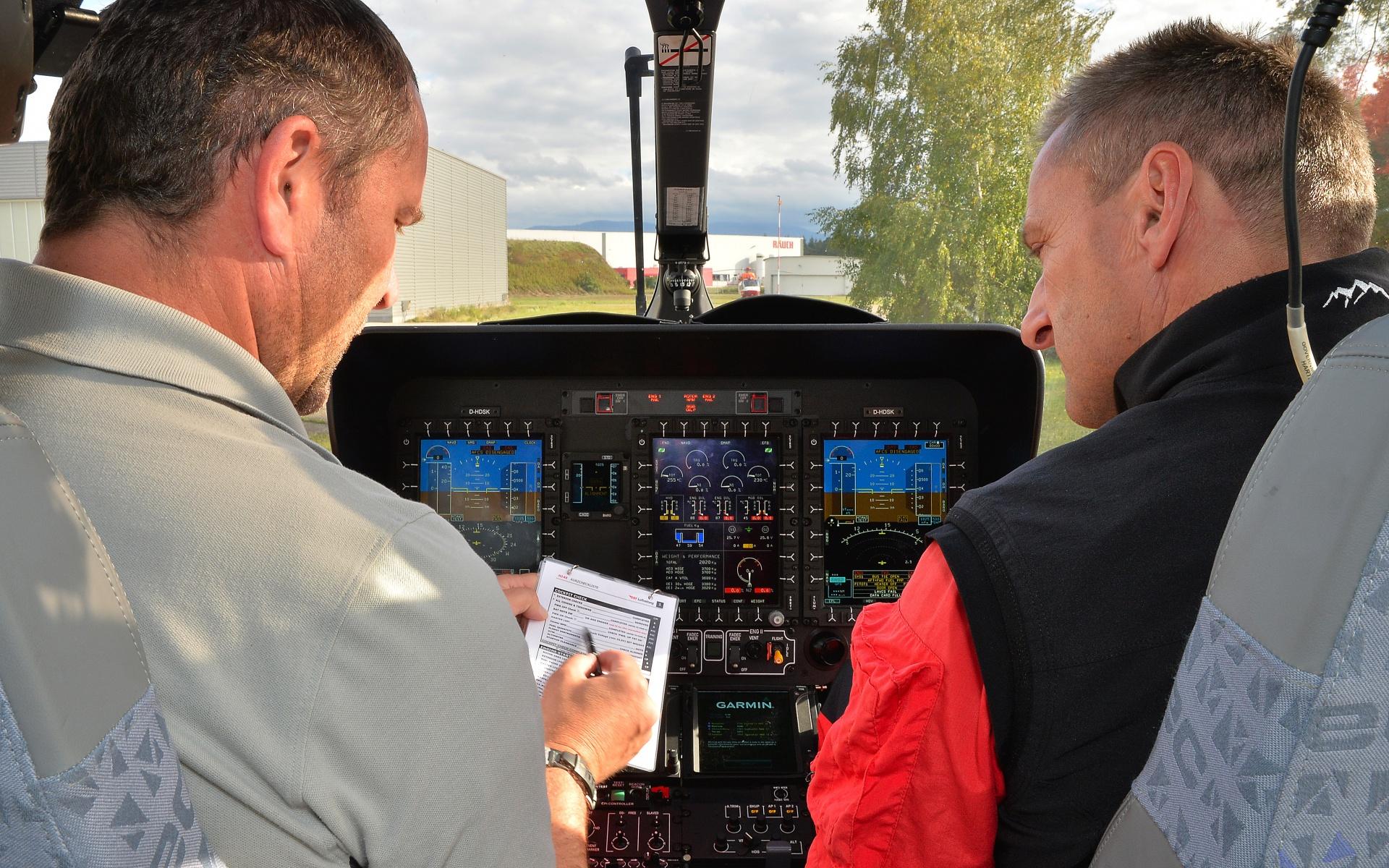 """Fluglehrer Jörg Redetzky (links) war einer der ersten beiden Piloten der DRF Luftrettung, der auf der H 135 geschult wurde. Nun gibt er sein Wissen rund um die vielfältigen Möglichkeiten des Glascockpits, das ebenso in der im Zuge der Flottenerneuerung beschafften H 145 zum Einsatz kommt, bei der """"Unterschiedsschulung"""" an seine Piloten-Kollegen wie den Chef der in Österreich gelegenen Station Reutte Christian Brunnlechner weiter."""
