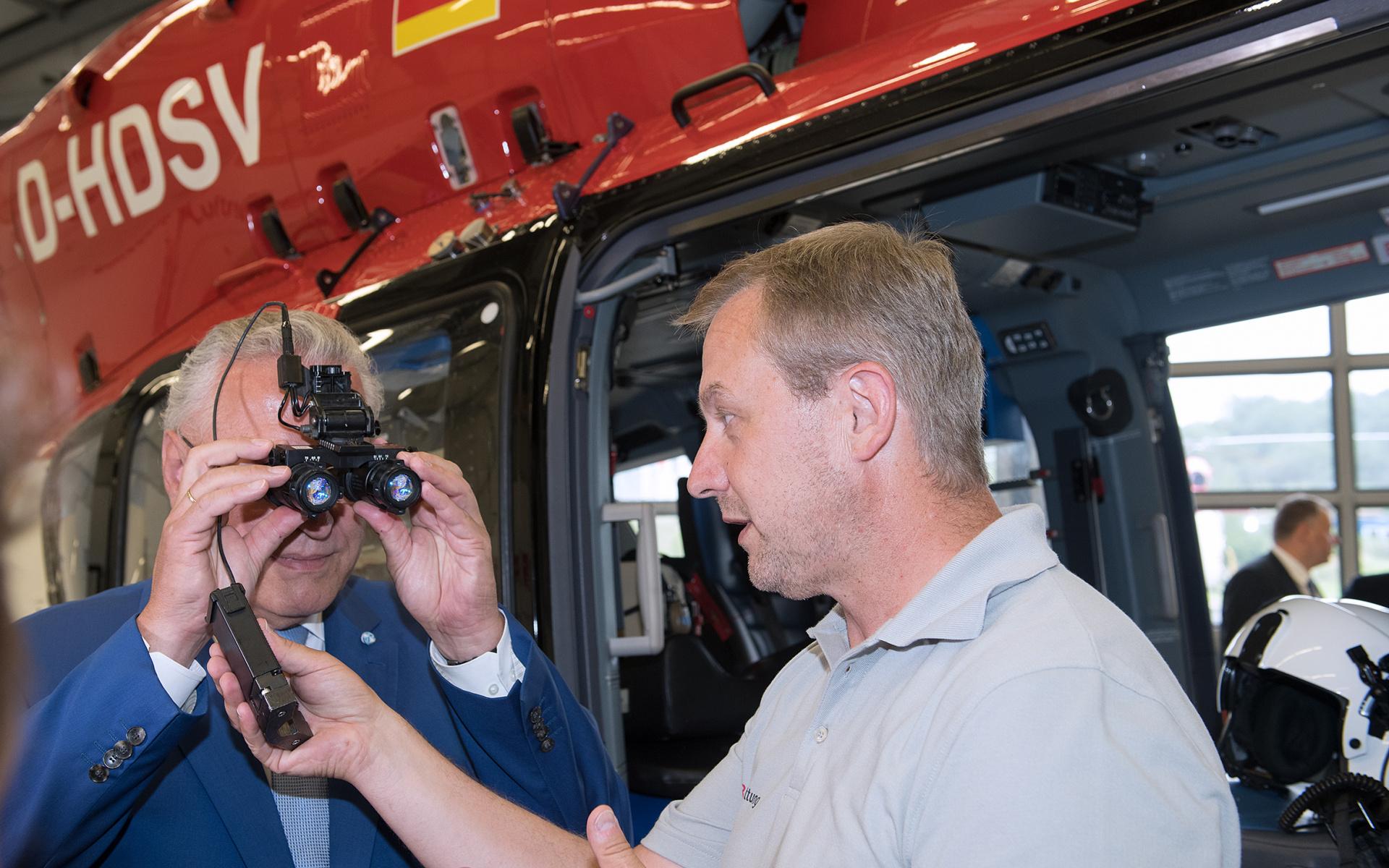 Der bayerische Innenminister testet eine Nachtsichtbrille (NVG). Quelle: DRF Luftrettung / LMU-Klinikum