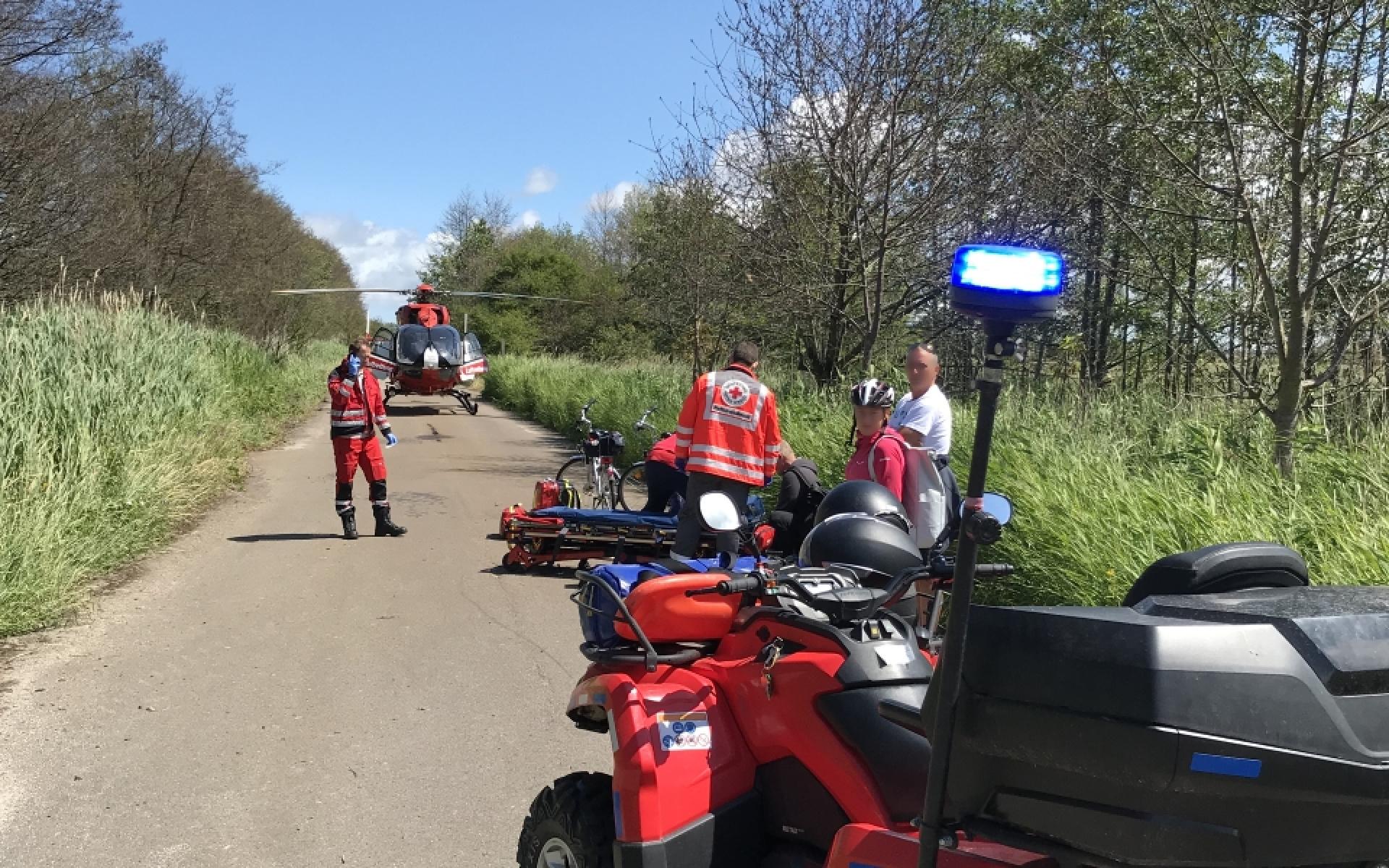 Christoph 47 der DRF Luftrettung steht auf einem Fahrradweg während eine gestürzte Radfahrerin versorgt wird.
