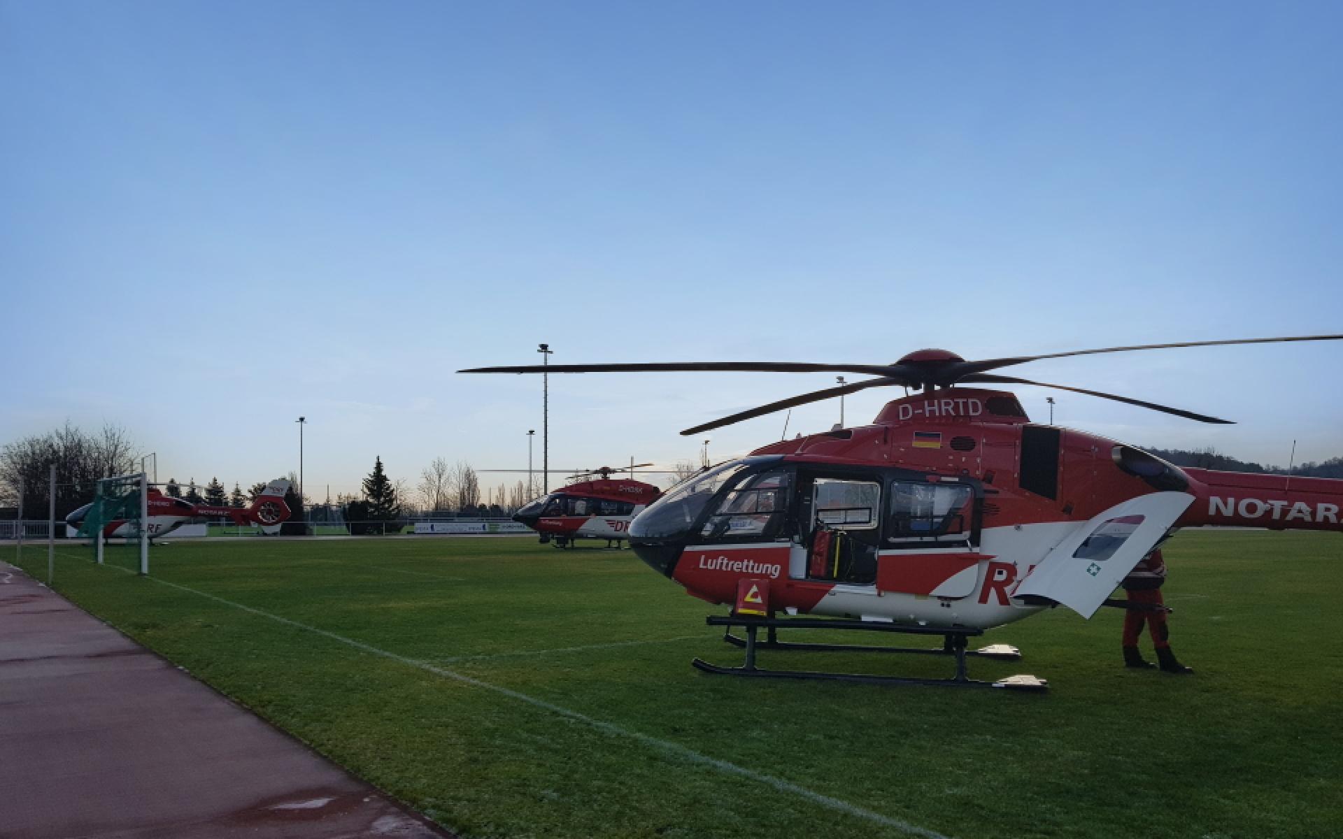 Drei Rettungshubschrauber der DRF Luftrettung stehen auf einem Sportplatz nebeneinander.