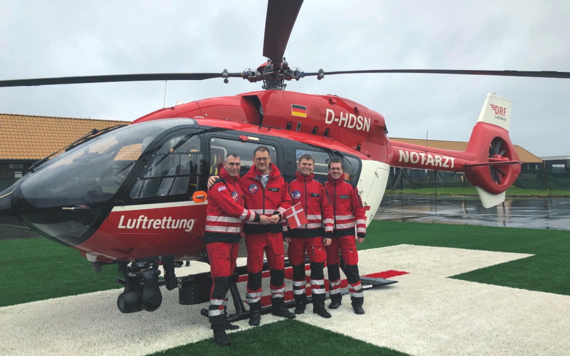 Die Crew eines Rettungshubschraubers der DRF Luftrettung steht vor einem Hubschrauber.