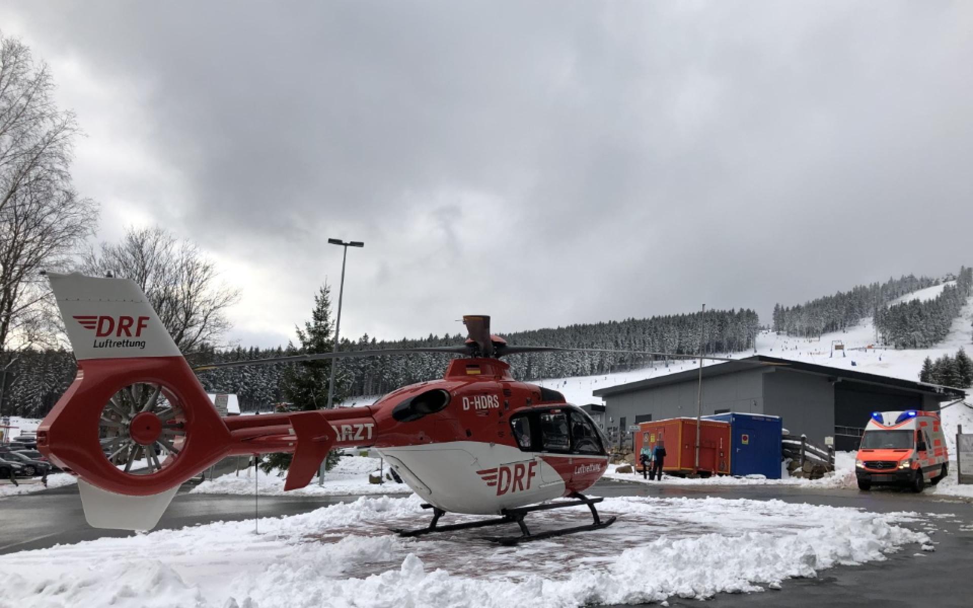 Ein Rettungshubschrauber der DRF Luftrettung steht an der Talstation eines Skigebiets.