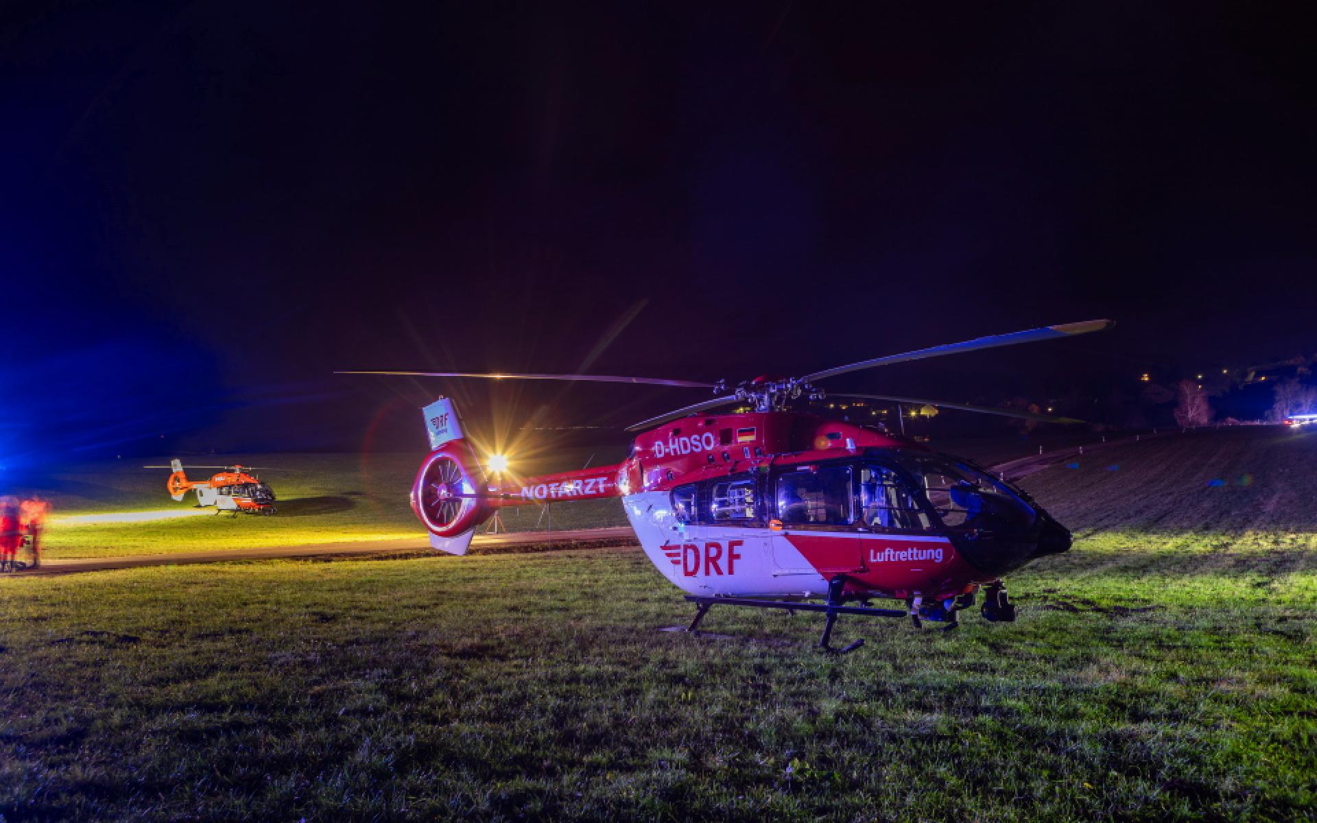 Die Intensivtransporthubschrauber Christoph Nürnberg und Christoph Regensburg stehen auf einer Wiese bei Nacht (Foto: Ralph Goppelt).