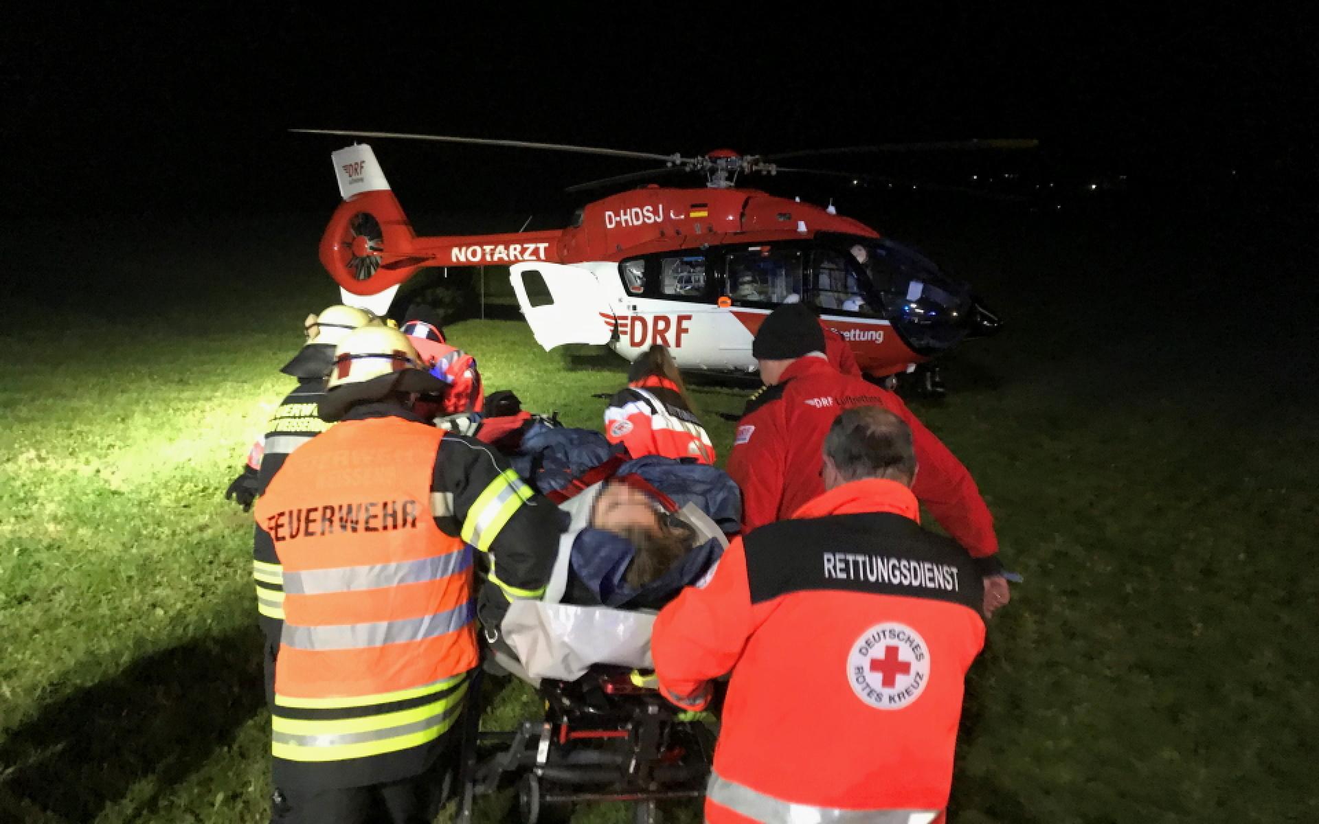 Eine Patientin wird bei Dunkelheit auf einen Intensivtransporthubschrauber auf einer Liege zugeschoben (Foto: DRF Luftrettung).