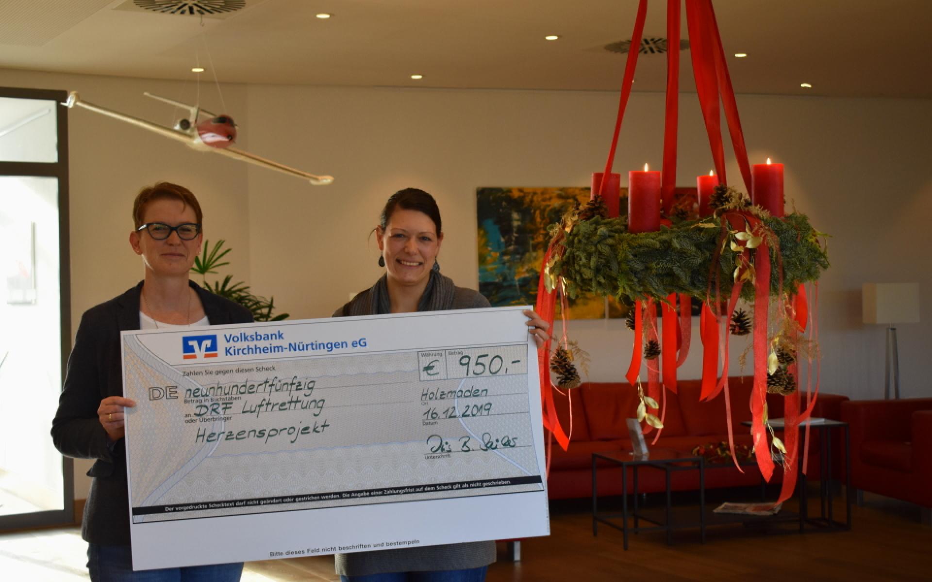 Bei einer Spendenübergabe halten zwei Frauen einen symbolischen Scheck in die Höhe.