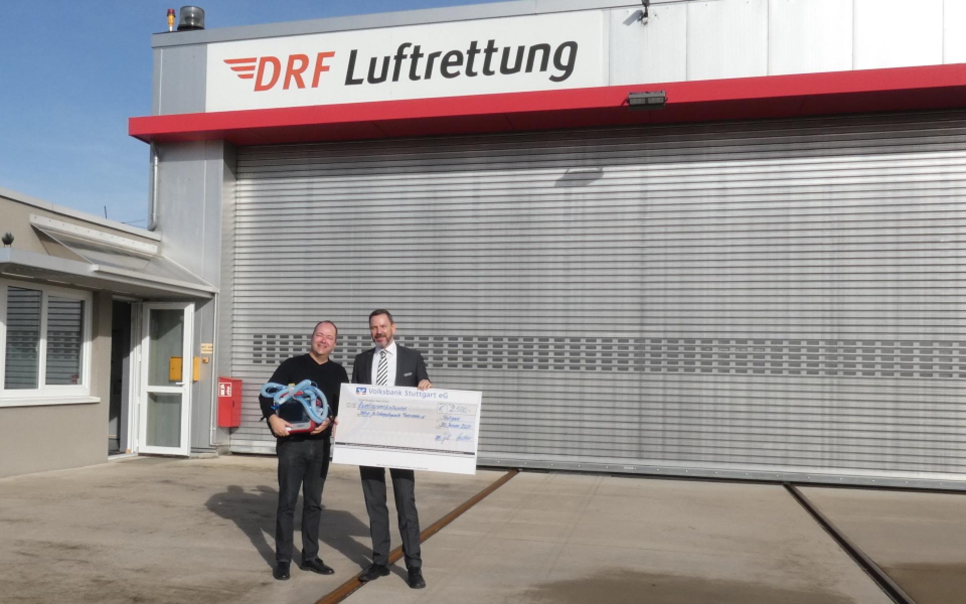 Zwei Männer stehen vor einem Hangar der DRF Luftrettung mit einem großen symbolischen Scheck in der Hand.