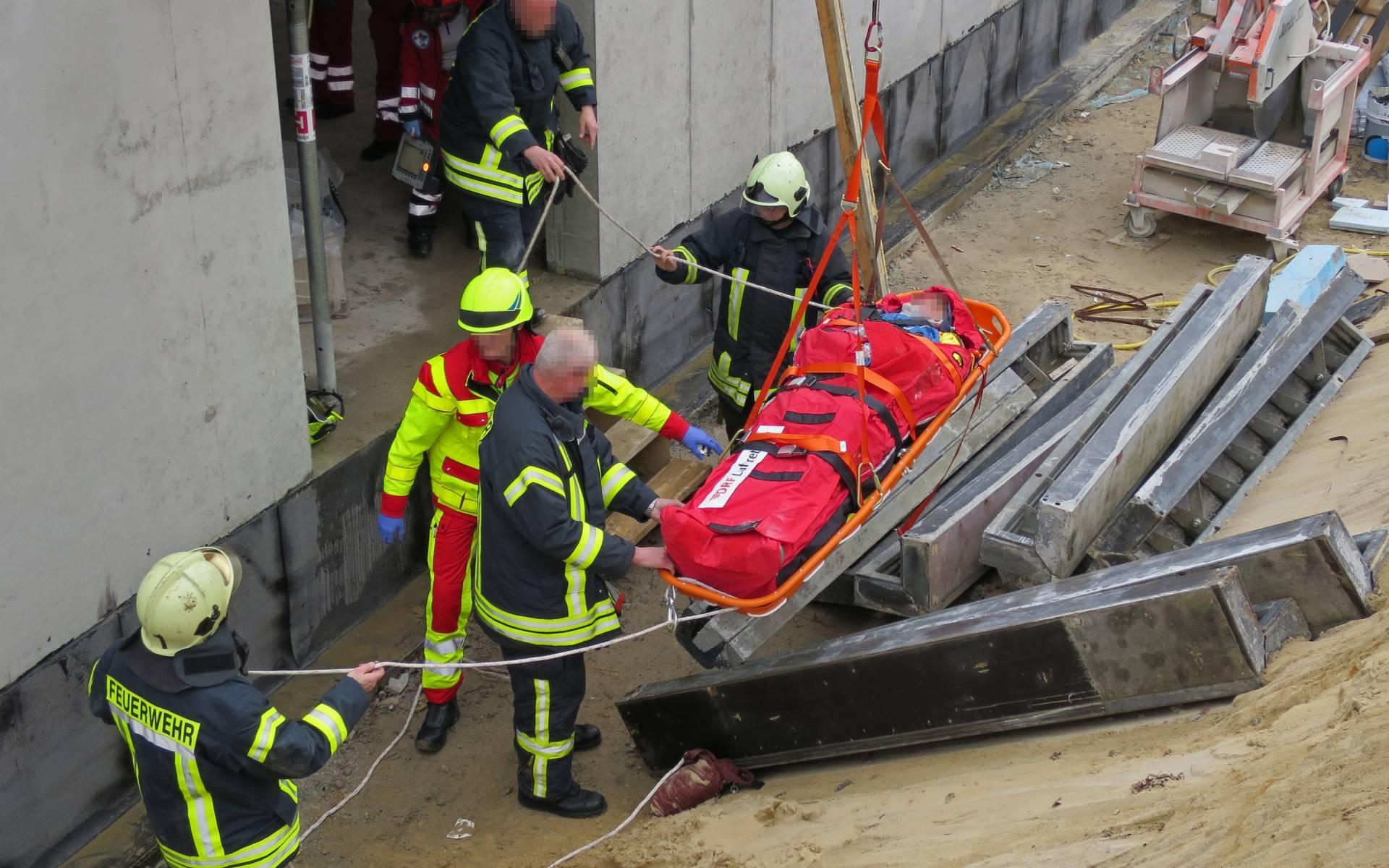 Transport aus der Baugrube: Die Rettungskräfte arbeiten Hand in Hand, um den Patienten mit einer Drehleiter nach oben zu heben.