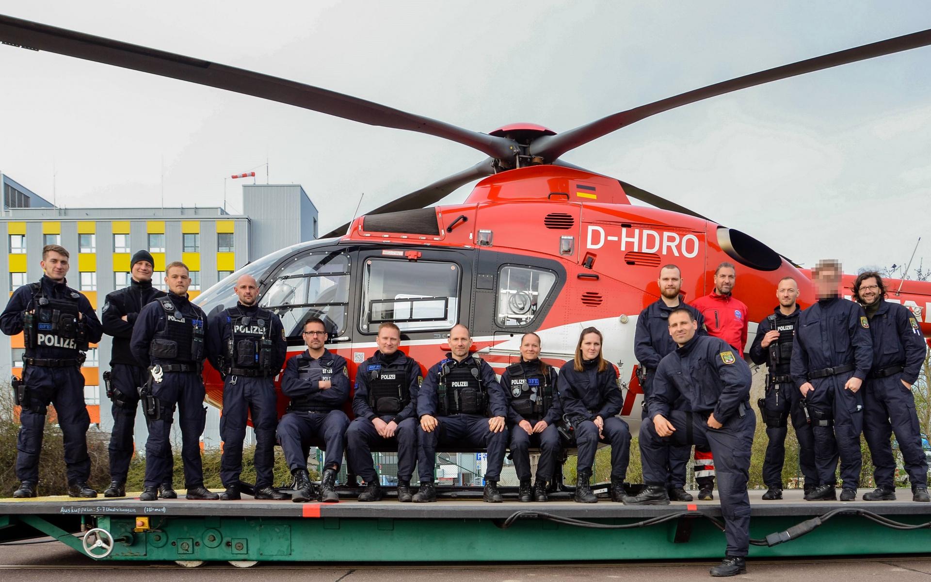 Gruppenbild mit Hubschrauber zum Abschluss des Besuchs.