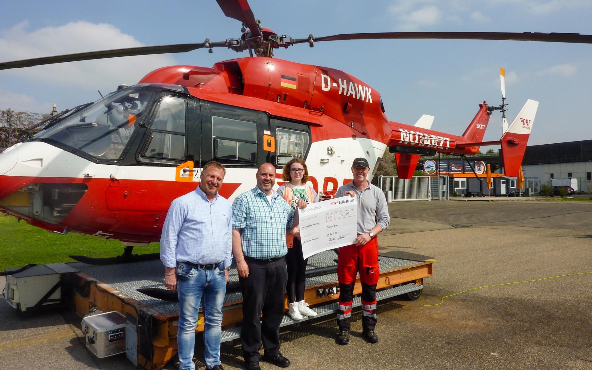 Harald Potsch übergibt der DRF Luftrettung seine Spende vor dem Hubschrauber der Mannheimer Station.