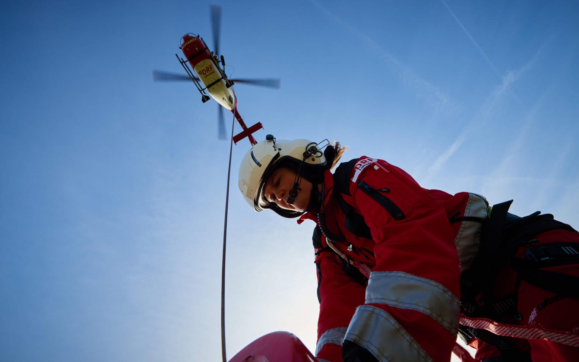 Der Pilot hält den Hubschrauber in der Luft über der Einsatzstelle, während die Winde am Bergesack befestigt wird.