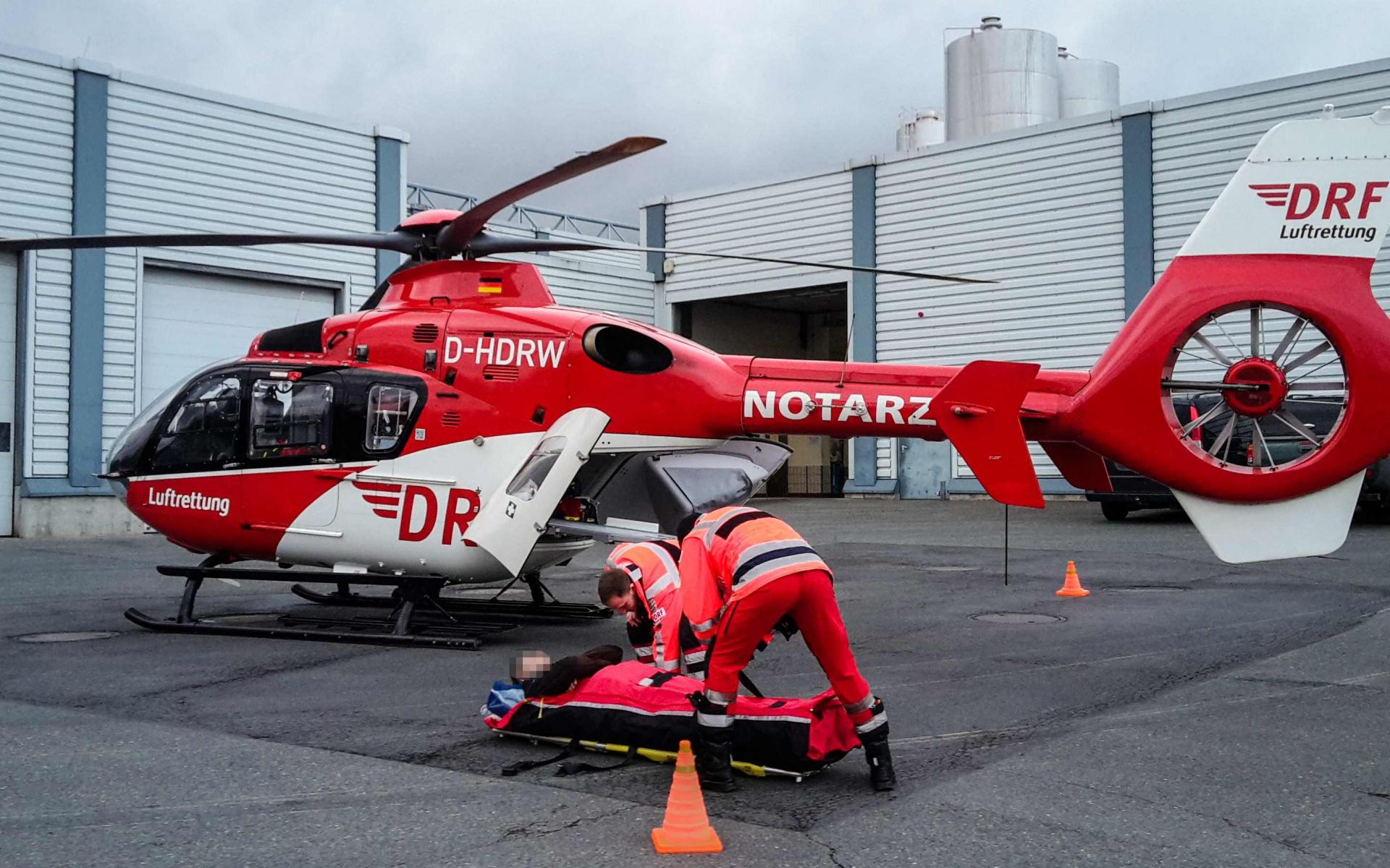 Notarzt und Rettungsassistent bereiten den verletzten Arbeiter auf den Flug ins Krankenhaus vor.
