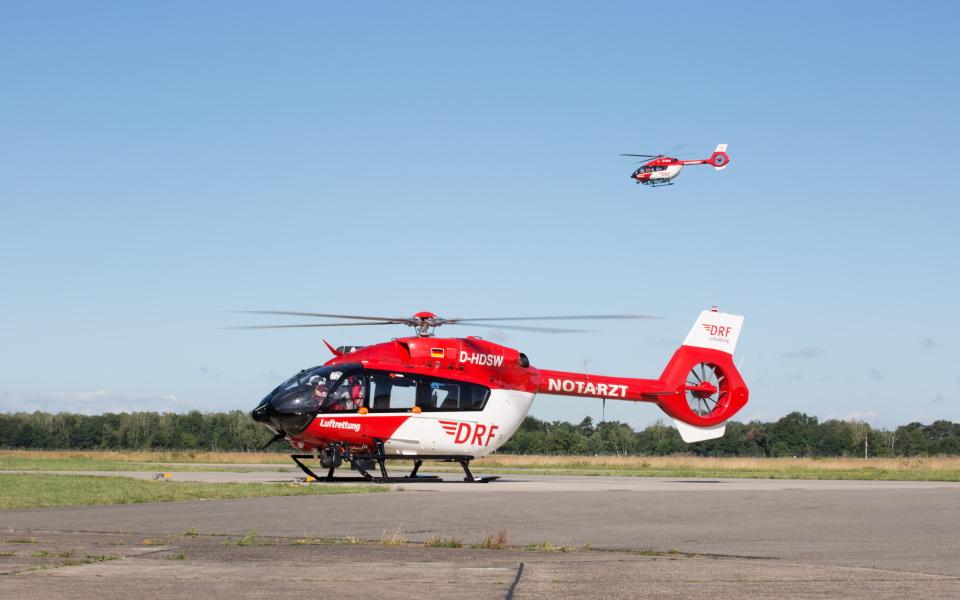 Ein Hubschrauber der DRF Luftrettung steht am Boden, im Hintergrund startet ein weiterer Hubschrauber zu einem Einsatz.
