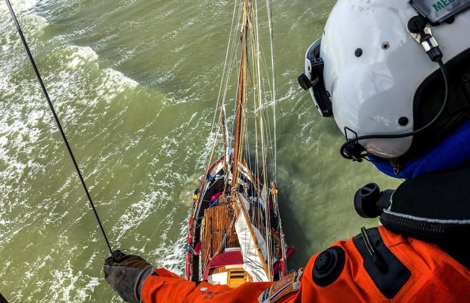 """Per Winde lässt sich der Notfallsanitäter vom NHC-Rettungshubschraubers bei starkem Wind bis zu sechs Beaufort auf den gestrandeten Traditionssegler absetzen. Im Doppelwinschverfahren wird der Segler an Bord der """"Northern Rescue 01"""" gerettet. Foto: NHC Northern Helicopter"""