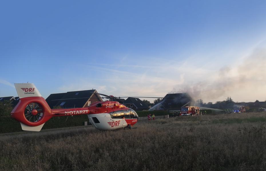 Ein Rettungshubschrauber der DRF Luftrettung steht an einem Ortrand bei einem Einsatz.