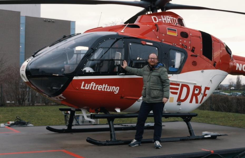 Doktor Allwissend steht vor einem Rettungshubschrauber der DRF Luftrettung
