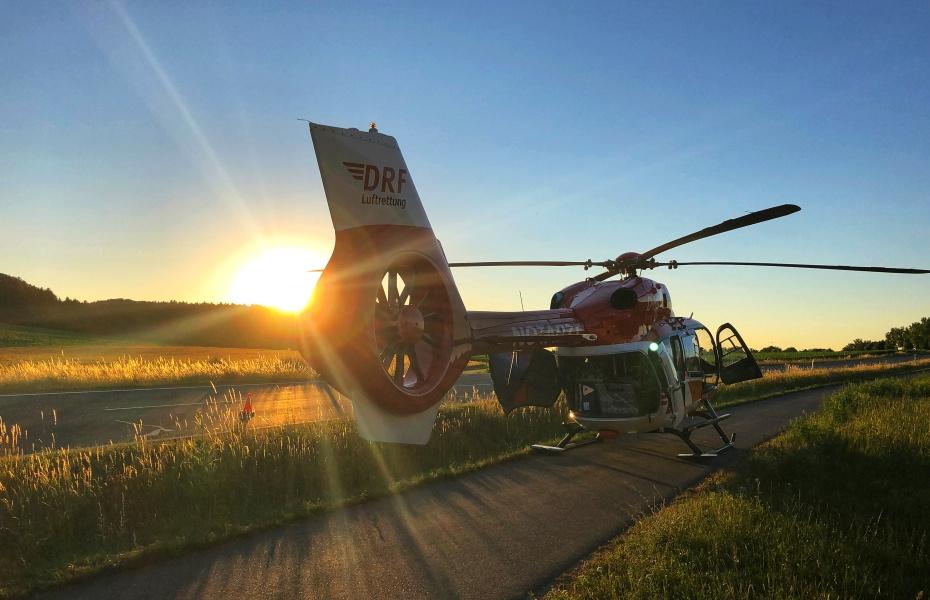 Ein rot-weißer Hubschrauber der DRF Luftrettung steht bei Sonnenuntergang auf einem Feldweg