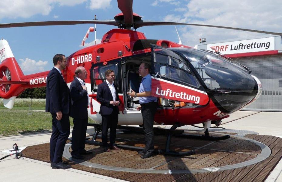 Michael Schmidt (links) und Dr. Gregor Lichy (rechts) geben Staatssekretär Wilfried Klenk (2.v.l.) und dem Landtagsabgeordneten Fabian Gramling (2.v.r.) Einblicke in die Arbeit der DRF Luftrettung.