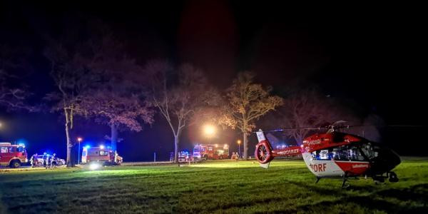 Der Intensivtransporthubschrauber Christoph Berlin steht bei Nacht auf einer Wiese neben einer Unfallstelle.