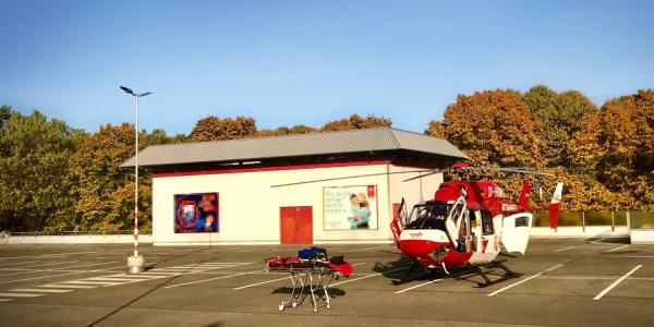 Ein Hubschrauber der DRF Luftrettung und eine Patiententrage stehen auf einem leeren Parkdeck.