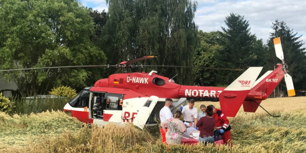 Christoph Dortmund der DRF Luftrettung steht in einem Getreidefeld