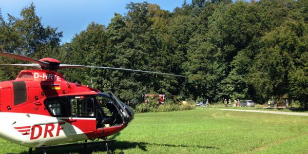 Der rot-weiße Rettungshubschrauber der DRF Luftrettung steht auf einer Wiese.