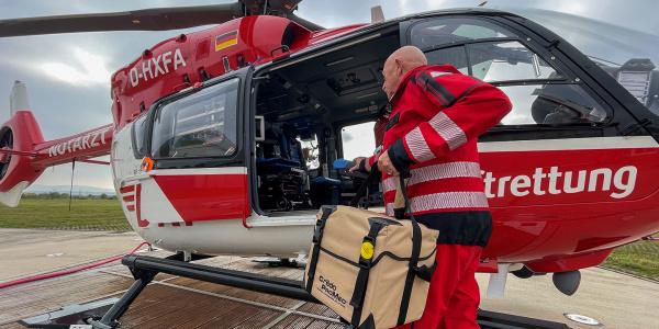 Ein Mann lädt eine Kühlbox in einen Hubschrauber ein. Quelle: DRF Luftrettung