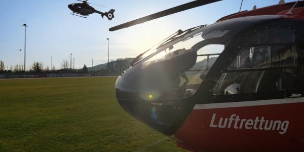 Im Vordergrund ein Rettungshubschrauber der DRF Luftrettung sowie ein weiterer Rettungshubschrauber im Flug.