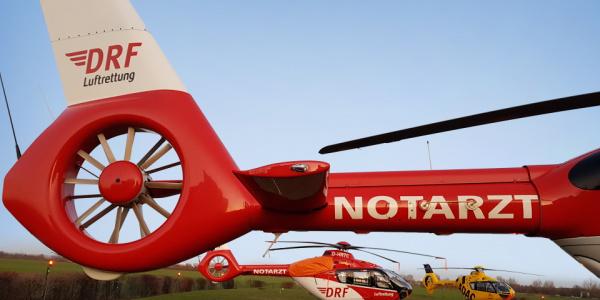 Zwei Rettungshubschrauber der DRF Luftrettung sowie ein weiterer Hubschrauber stehen auf Landeplätzen und im Rasen.