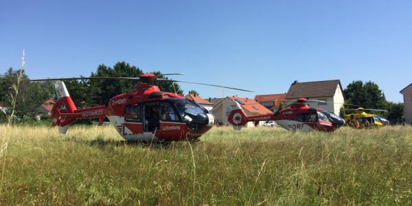 Zwei Hubschrauber der DRF Luftrettung stehen auf einer Wiese