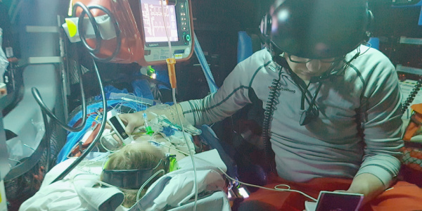 Hubschraubernotarzt Dr. Christian Siebers untersucht das kleine Mädchen während des Fluges mit einem mobilen Ultraschallgerät.