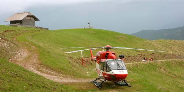 Unweit des gestürzten Mountainbikers landet Pilot Jürgen Würtz den rot-weißen Rettungshubschrauber und die Flugretter eilen zu dem Schwerverletzten.