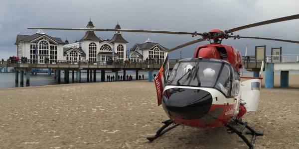 Der Rettungshubschrauber der DRF Luftrettung nutzt den Strand bei der Selliner Seebrücke als Landeplatz während eines Einsatzes.