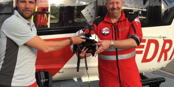 Stationsleiter Bernd Rosenberger (rechts) übergibt den Pilotenhelm mit Nachtsichtgerät an Markus Freudenhagen, Regionalleiter Nord und an diesem Tag Co Pilot (Quelle DRF Luftrettung).