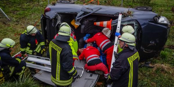 Während die Feuerwehr noch mit der Befreiung der Frau aus dem Auto beschäftigt ist, versorgen Notarzt und Notfallsanitäter der DRF Luftrettung bereits die Schwerverletzte.