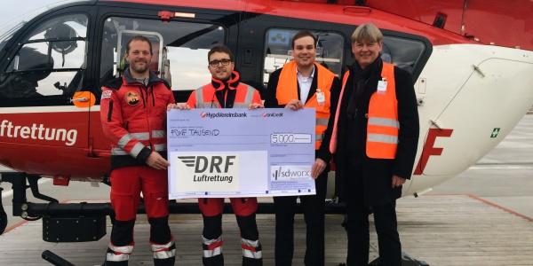 Übergabe des Spendenschecks am Hubschrauber: Pilot Tilman Blaich (DRF Luftrettung), Rettungsassistent Thiemo Richter (DRF Luftrettung), Michael Rößle (SC Worx), Wolfgang Schwab (SC Worx).